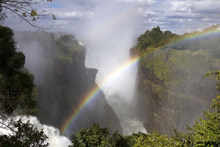 Regenboog in de Victoria watervallen Zimbabwe