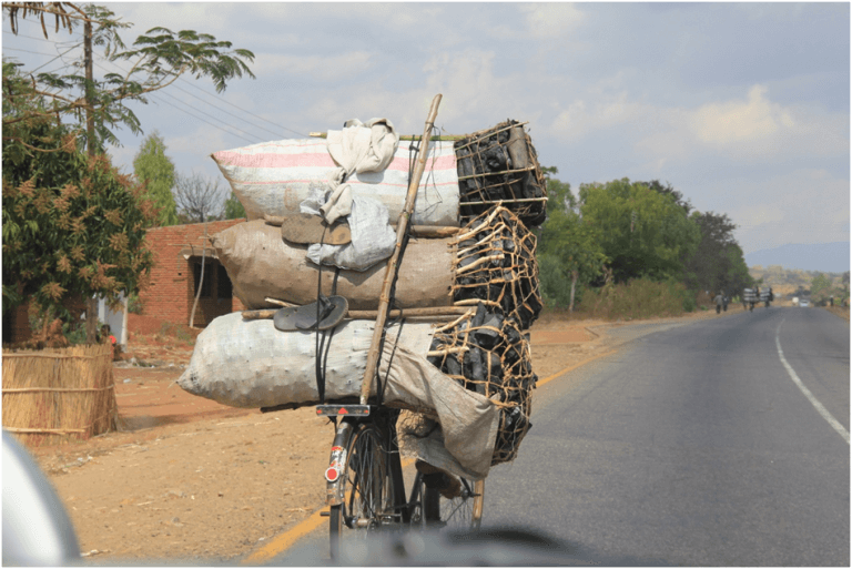 Eenzame fietser met zakken houtskool in Malawi